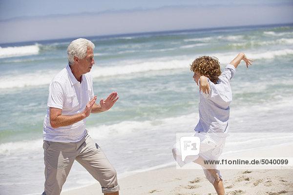Älterer Mann  der seinem Enkel Kampfkunst beibringt.