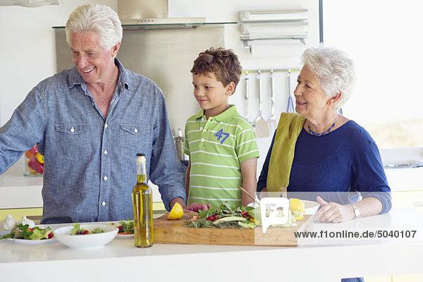 Seniorenpaar bei der Zubereitung des Essens mit ihrem Enkel
