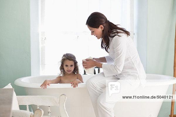 Frau  die ihrer Tochter ein Bad gibt.