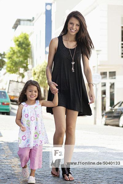 Porträt einer schönen jungen Frau mit ihrer süßen kleinen Tochter beim Spaziergang