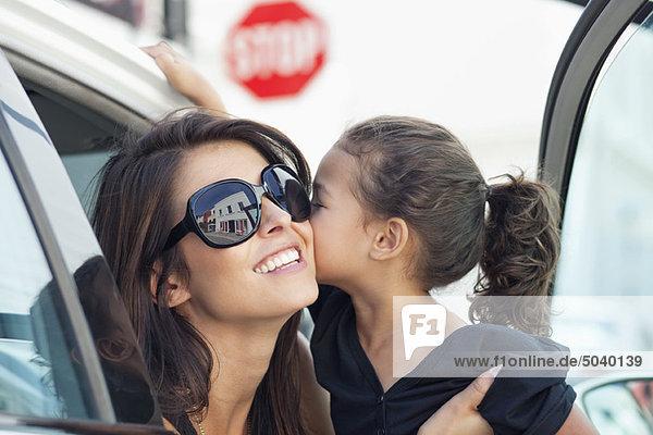 Schöne junge Frau mit ihrer süßen kleinen Tochter  die sich im Auto küsst.
