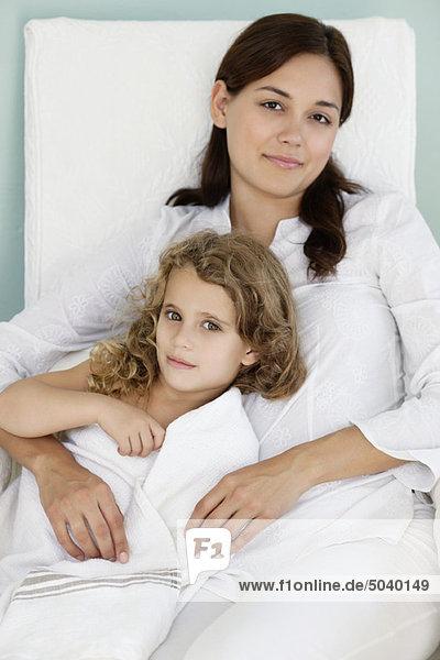 Porträt einer jungen Frau  die mit ihrer Tochter in weißes Handtuch gehüllt liegt.