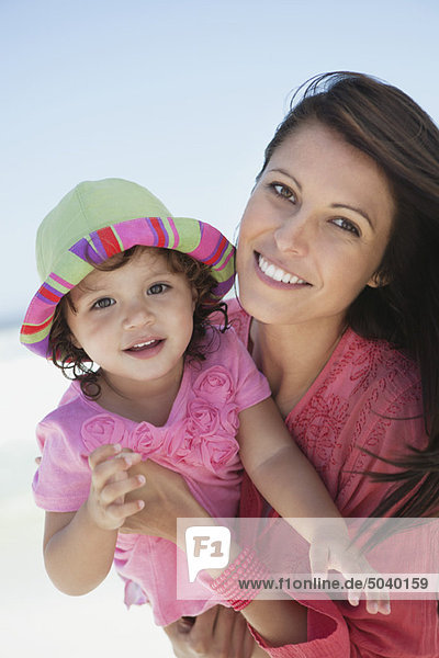 Woman enjoying on the beach with her daughter