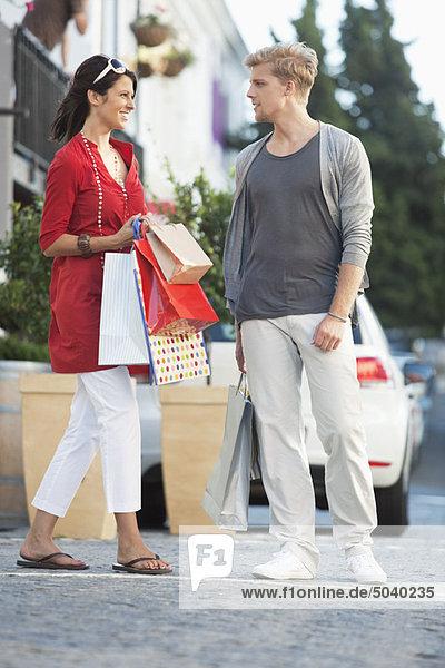 Junges Paar  das sich mit Einkaufstaschen auf der Straße ansieht