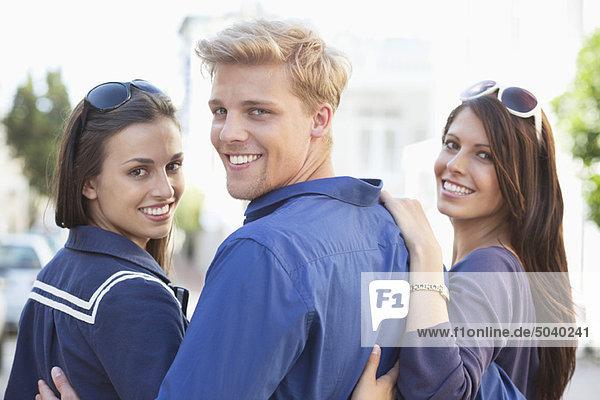 Porträt eines jungen Mannes mit zwei lächelnden Frauen