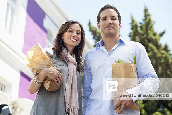 Porträt eines Paares stehend mit Papiertüten voller Gemüse