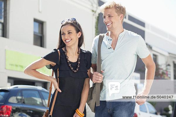 Lächelndes junges Paar auf einer Straße stehend