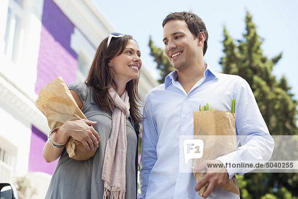 Lächelndes Paar  das sich mit Papiertüten voller Gemüse ansieht.