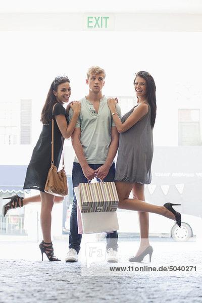 Zwei junge Frauen  die mit den Händen auf den Schultern des Mannes stehen.
