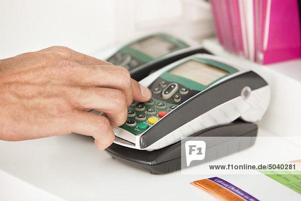Verkäufer mit einem Kreditkartenleser am Schalter