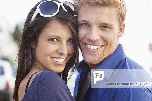 Porträt eines jungen Paares  das sich umarmt und lächelt