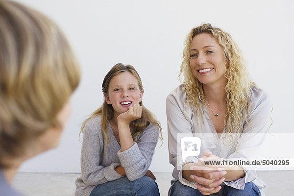 Mittlere erwachsene Frau im Gespräch mit ihrem Sohn und ihrer Tochter zu Hause