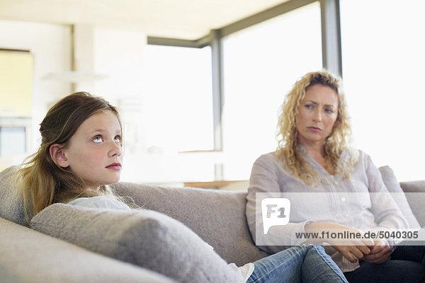 Mittlere erwachsene Frau und ihre Tochter sitzen auf einer Couch.