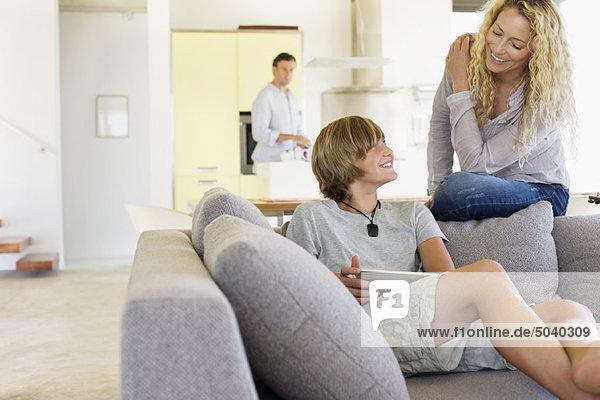 Teenager-Junge  der ein digitales Tablett benutzt und mit seiner Mutter redet.