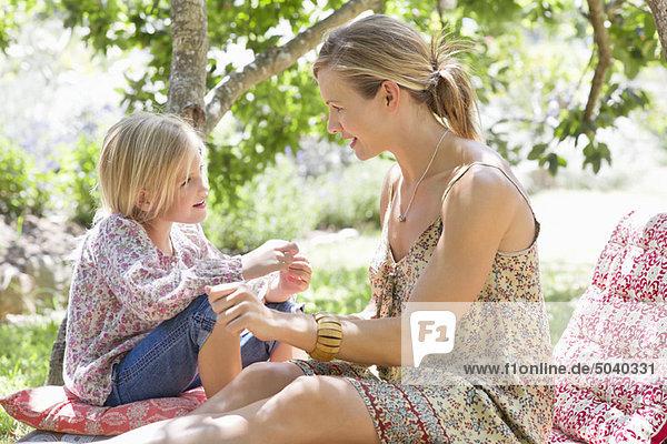 Seitenprofil der Mutter und eines kleinen Mädchens  die sich im Freien sehen.