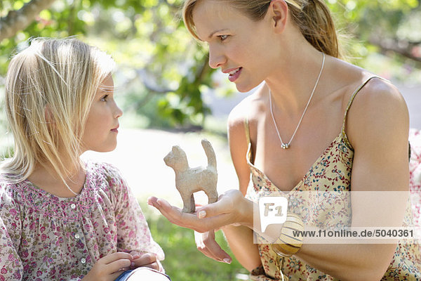 Little girl and her mother with a toy in hand outdoors