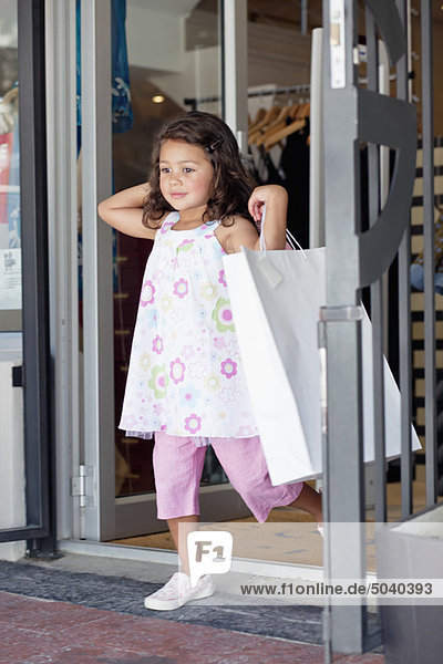Cute little girl walking out of a shopping mall with shopping bags