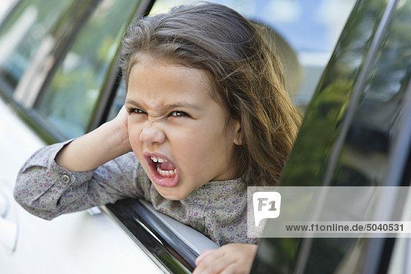 Süßes kleines Mädchen  das aus dem Autofenster schaut.