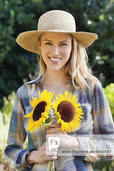 Porträt einer jungen Frau mit Sonnenblumen im Feld