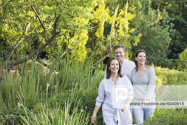 Mature couple walking with their mother in a garden
