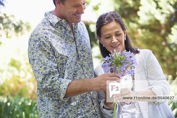 Ein Mann  der seiner Mutter eine Blume schenkt und lächelt.