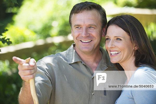 Lächelnder Mann  der seiner Frau im Freien etwas zeigt.