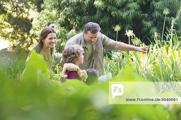 Zwei kleine Kinder  die mit ihren Eltern im Garten spazieren gehen.