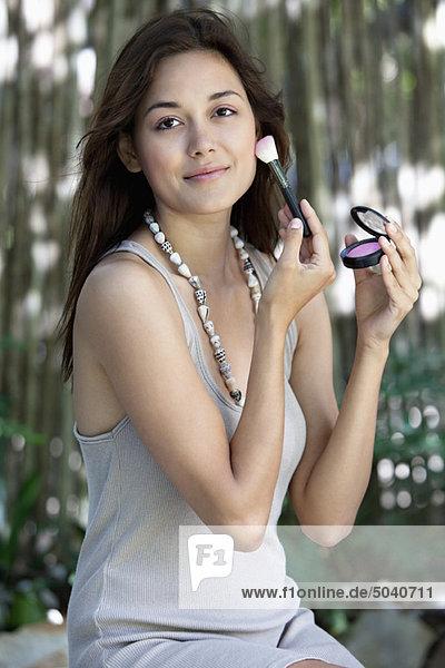 Porträt einer schönen jungen Frau beim Schminken