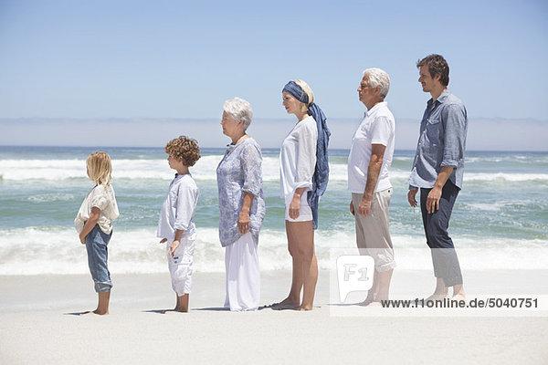 Familie steht in Reihe am Strand mit Kindern