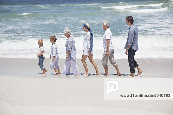 Familienspaziergang mit Kindern am Strand