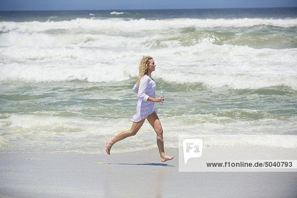 Seitenprofil einer schönen Frau  die am Strand läuft