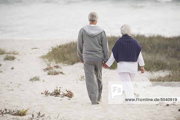 Rückansicht eines Seniorenpaares beim Spaziergang am Strand