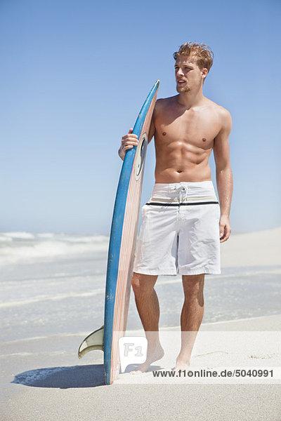 Mann am Strand stehend mit Surfbrett