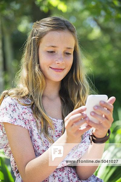 Lächelndes kleines Mädchen SMS mit Hilfe eines Mobiltelefons
