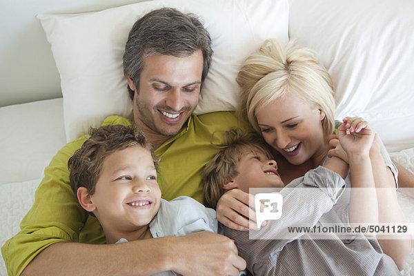 Paar mit ihren Kindern im Bett entspannen