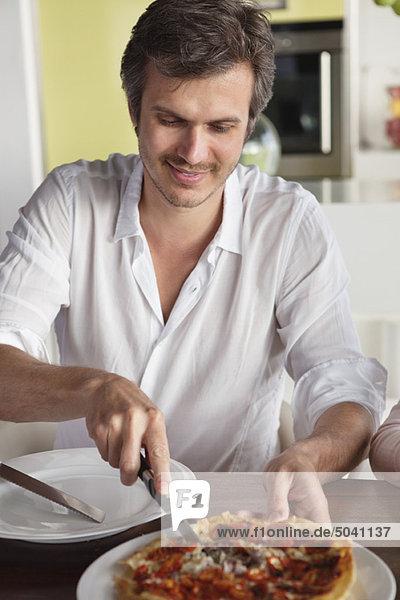 Mann beim Pizzaschneiden am Esstisch