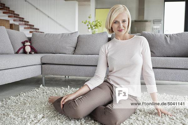 Porträt einer Frau auf einem Teppich sitzend