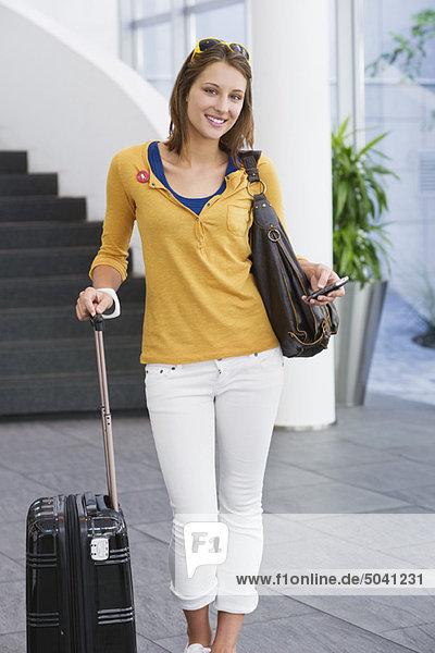 Porträt einer Frau mit Handy und Trolley-Tasche