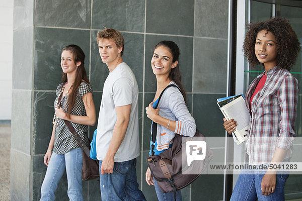 Portrait der auf dem Campus stehenden Studierenden