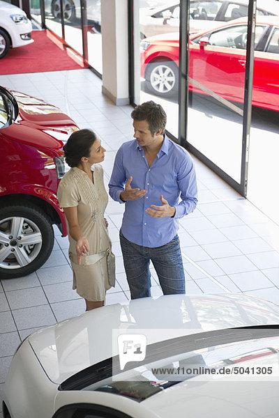 Verkäuferin  die das Auto dem mittleren Erwachsenen im Ausstellungsraum zeigt.