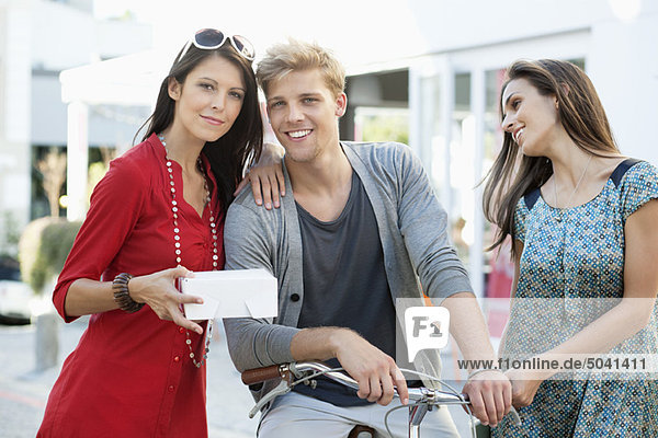Portrait eines jungen Mannes mit zwei Frauen beim Radfahren