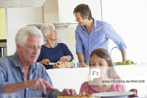 Mann beim Kuchenschneiden mit seiner Enkelin und seiner Frau im Gespräch mit ihrem Sohn im Hintergrund