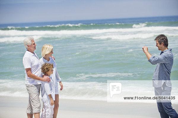 Mittlerer erwachsener Mann beim Fotografieren seiner Familie am Strand