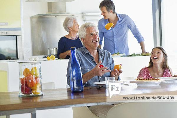 Älterer Mann lächelt mit seiner Enkelin am Esstisch