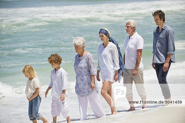 Mehrgenerationen-Familienwandern in einer Reihe am Strand