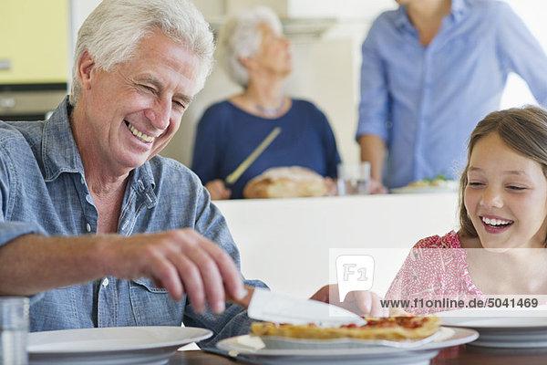 Mann schneidet Kuchen mit einem Messer und seine Enkelin sitzt neben ihm.