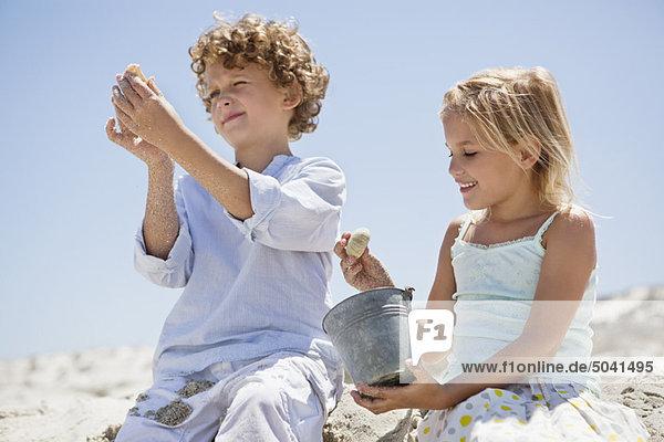 Bruder und Schwester beim Betrachten von Muscheln am Strand