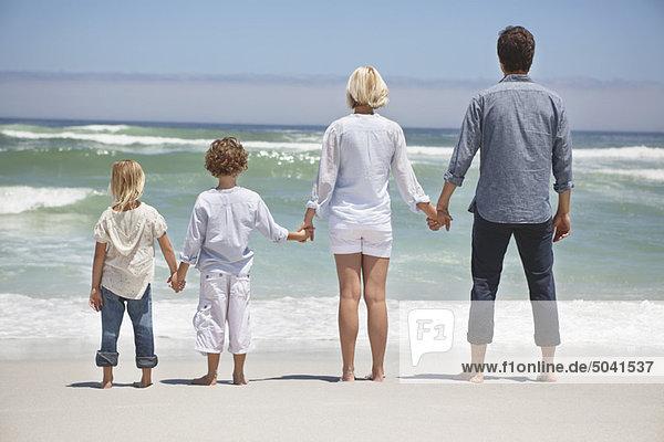 Familie mit Blick auf das Meer vom Strand aus