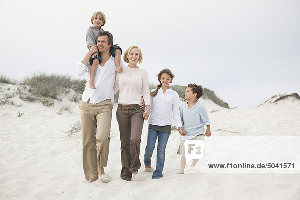 Ein Paar  das mit seinen Kindern am Strand spazieren geht.