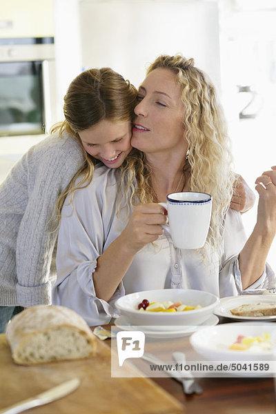 Mittlere erwachsene Frau  die ihre Tochter am Esstisch küsst.